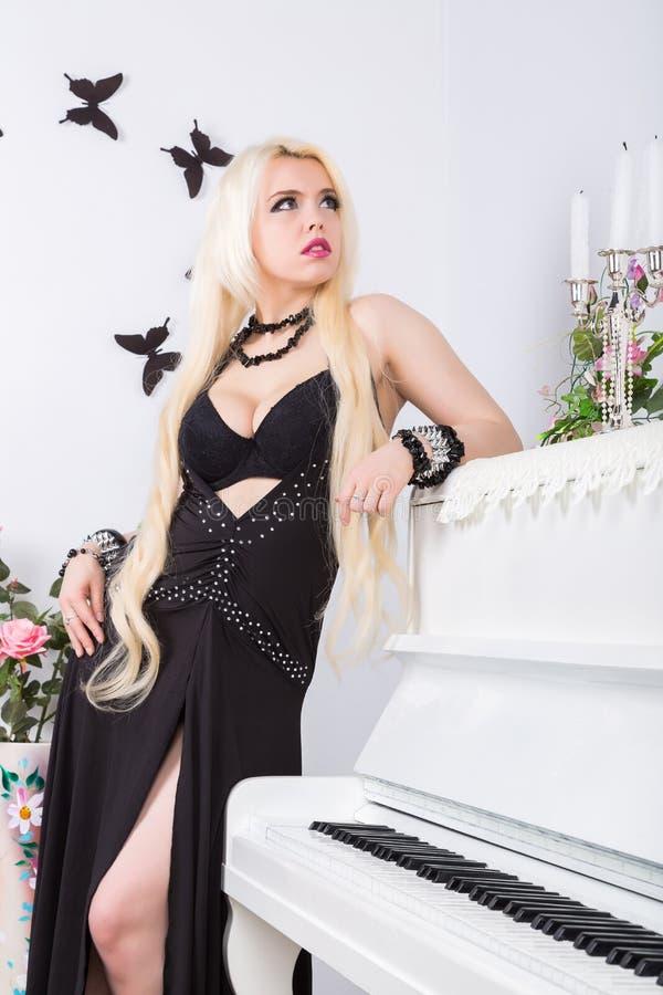 Mooie jonge aantrekkelijke vrouw in avondjurk en piano stock afbeeldingen