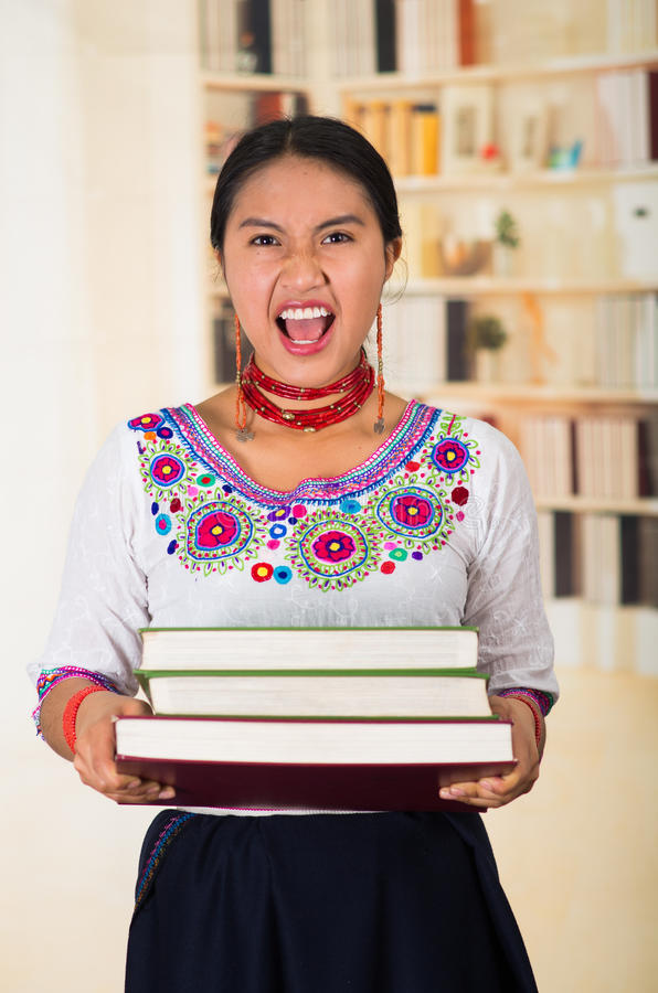 Mooie jonge advocaat die traditionele Andesblouse en rode halsband dragen, houdend stapel die boeken, uit gillen aan stock fotografie