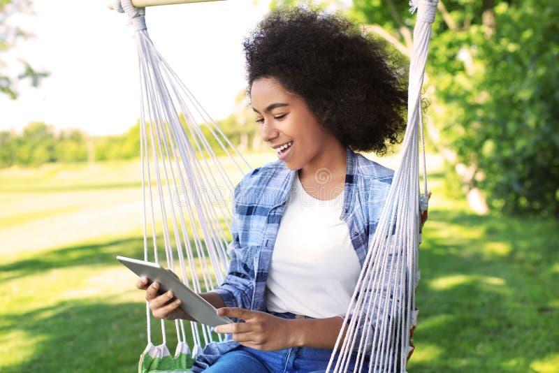 Mooie jonge Afrikaans-Amerikaanse vrouw met tabletcomputer die in hangmat in openlucht rusten stock afbeelding