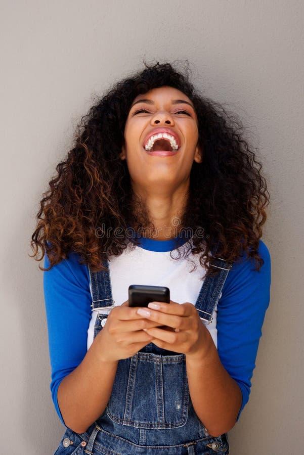 Mooie jonge Afrikaanse Amerikaanse vrouw die met cellphone lachen stock foto