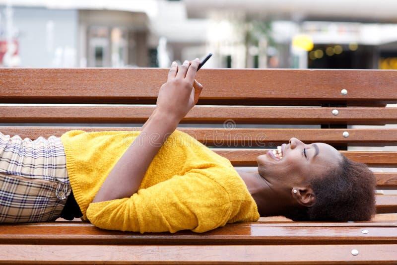 Mooie jonge Afrikaanse Amerikaanse vrouw die op bank liggen die mobiele telefoon bekijken royalty-vrije stock afbeelding