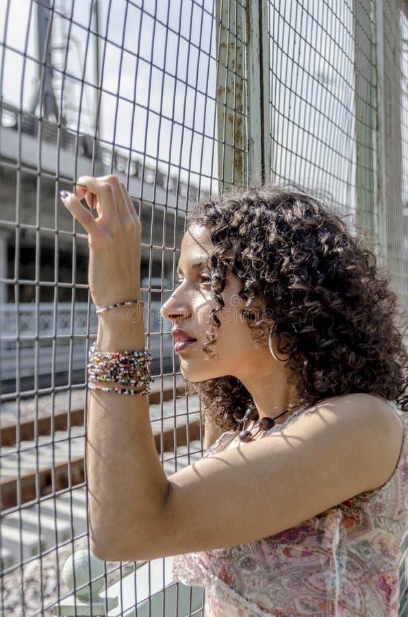 Mooie jonge Afrikaanse mulatvrouw in een de zomerkleding op een industriezone stock afbeelding
