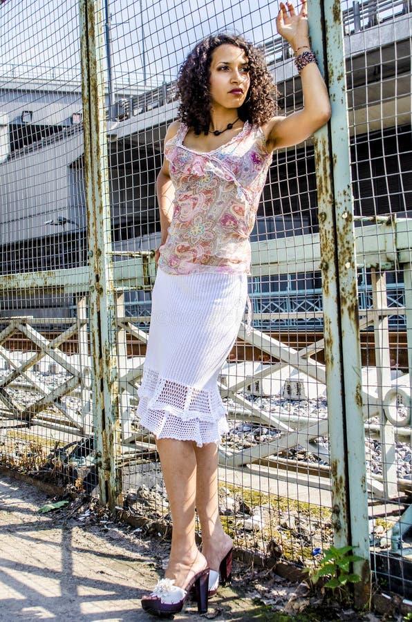 Mooie jonge Afrikaanse mulatvrouw in een de zomerkleding op een industriezone stock foto's