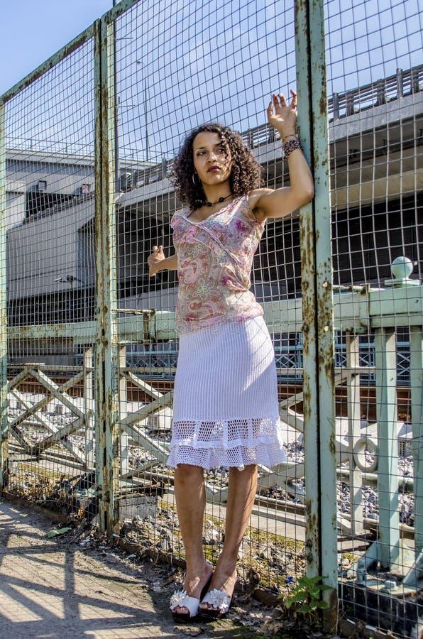 Mooie jonge Afrikaanse mulatvrouw in een de zomerkleding op een industriezone royalty-vrije stock fotografie