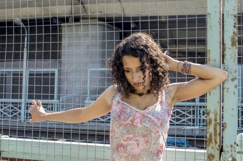 Mooie jonge Afrikaanse mulatvrouw in een de zomerkleding op een industriezone royalty-vrije stock foto's