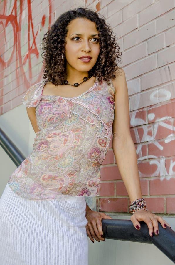 Mooie jonge Afrikaanse mulatvrouw in een de zomerkleding op een industriezone stock foto