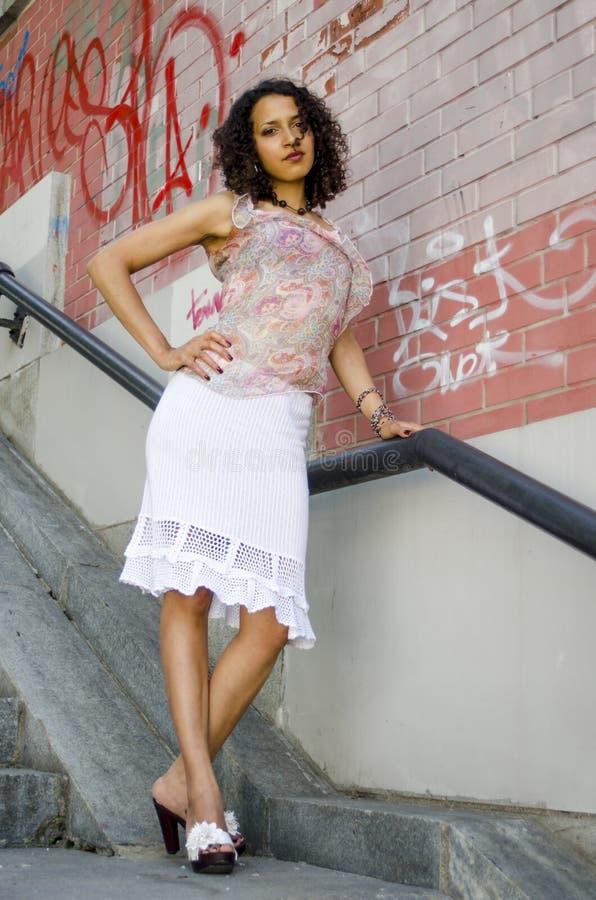 Mooie jonge Afrikaanse mulatvrouw in een de zomerkleding op een industriezone stock fotografie