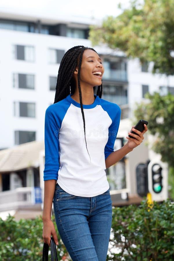 Mooie jonge Afrikaanse vrouw die in openlucht in de stad met cellphone lopen royalty-vrije stock afbeeldingen