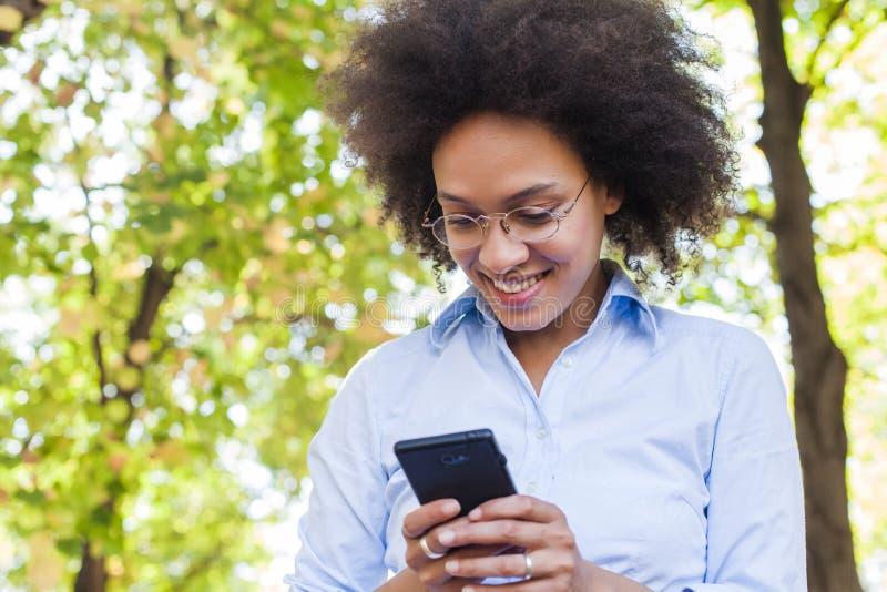 Mooie Jonge Afrikaanse Vrouw die Telefoon in Aard met behulp van royalty-vrije stock afbeelding
