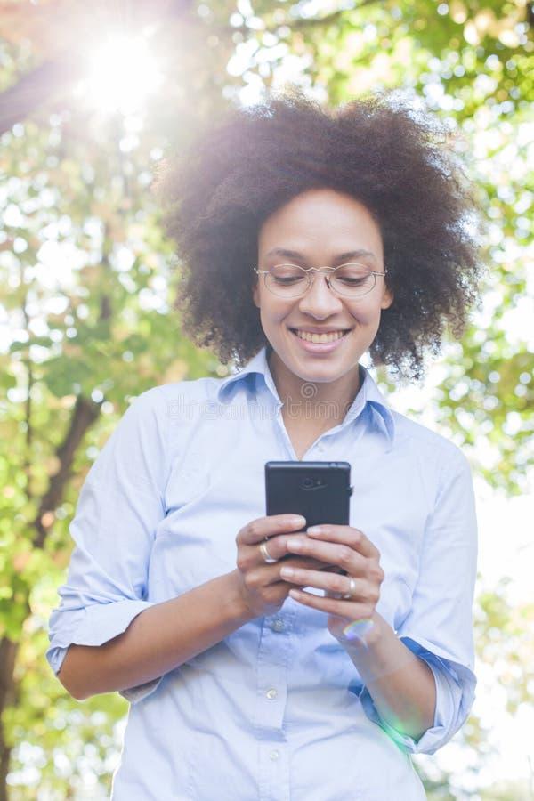 Mooie Jonge Afrikaanse Vrouw die Telefoon in Aard met behulp van royalty-vrije stock foto's