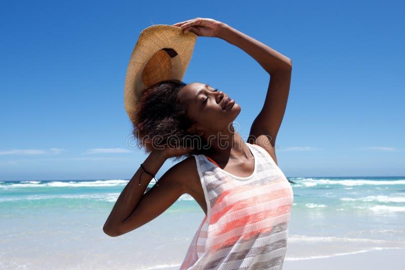 Mooie jonge Afrikaanse vrouw met hoed die in openlucht stellen stock afbeeldingen