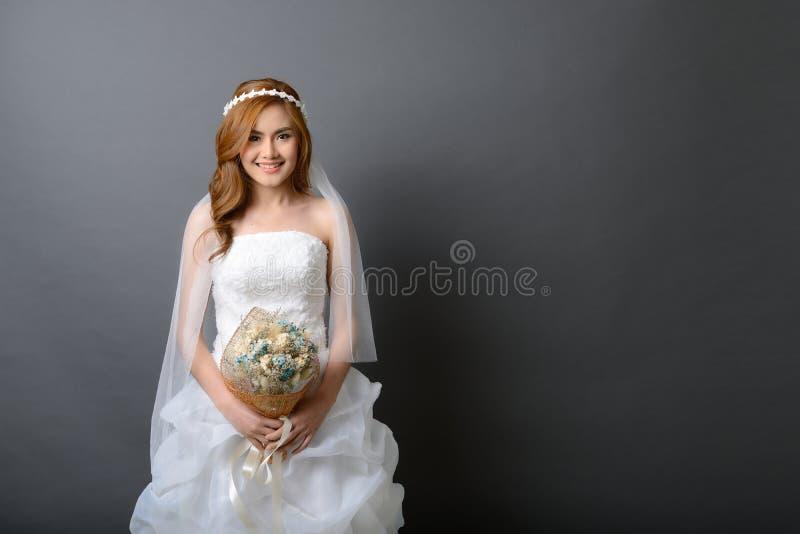 Mooie jonge Aziatische bruid in huwelijkskleding met bloemboeket royalty-vrije stock foto