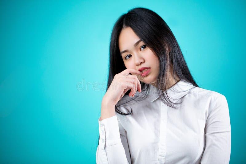 Mooie jonge Aziatische die vrouw op blauwe achtergrond wordt geïsoleerd gezichts stock afbeeldingen