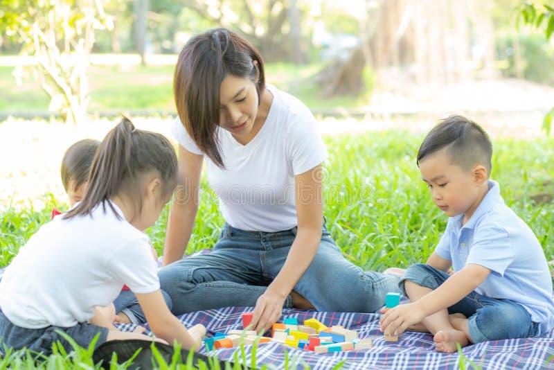 Mooie jonge Aziatische mamma en dochter speelstuk speelgoed blokken voor het leren van ontwikkeling gelukkig en pret bij park in  royalty-vrije stock afbeeldingen