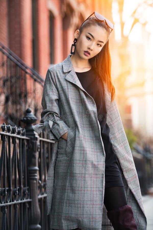 Mooie jonge Aziatische mannequinvrouw die op stadsstraat lopen die jasje en zonnebril dragen stock foto
