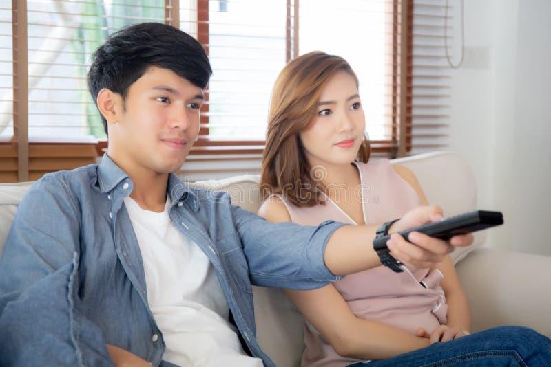 Mooie jonge Aziatische paarholding verre en het letten op TV of de video die op bank stromen met ontspant en gelukkig thuis in wo royalty-vrije stock foto's