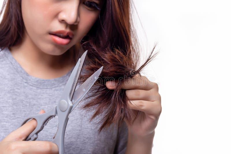 Mooie jonge Aziatische vrouw die of haar gespleten punten van haareinden in orde maken snijden De aantrekkelijke mooie jonge dame stock foto's