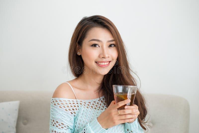 Mooie jonge Aziatische vrouw die haar ochtendthee over een brea drinken royalty-vrije stock afbeeldingen