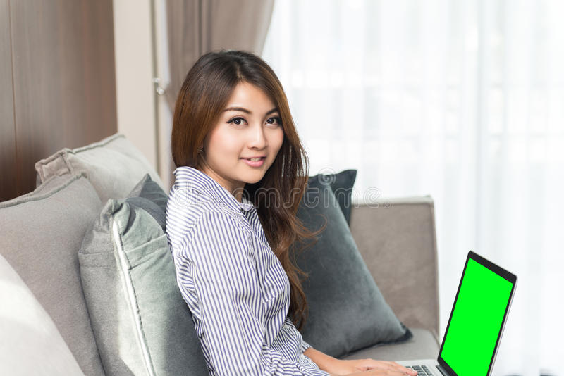 Mooie jonge Aziatische vrouw die laptop op bank in de woonkamer met behulp van royalty-vrije stock foto's