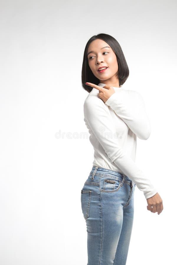 Mooie jonge Aziatische vrouw die op whitespace richten stock fotografie