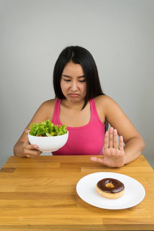 Mooie jonge Aziatische vrouw die saladekom kiezen en chocoladedoughnut verwerpen royalty-vrije stock afbeelding