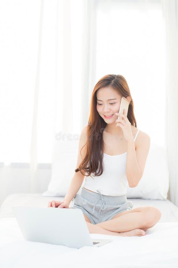 Mooie jonge Aziatische vrouw gebruikend laptop en sprekend slimme mobiele telefoon voor vrije tijd op slaapkamer stock fotografie