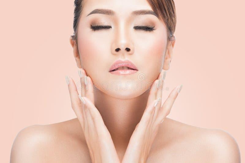 Mooie jonge Aziatische vrouw met gesloten ogen wat betreft haar gezicht royalty-vrije stock fotografie