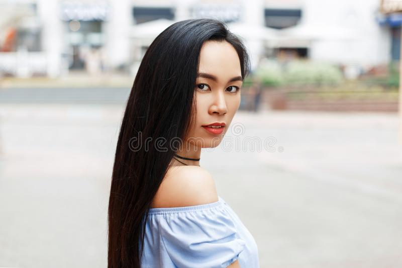 Mooie jonge Aziatische vrouw met naakte schouders in de stad royalty-vrije stock afbeelding