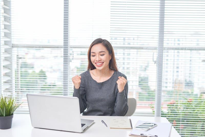 Mooie jonge Aziatische vrouw met opgewekt laptop royalty-vrije stock foto's