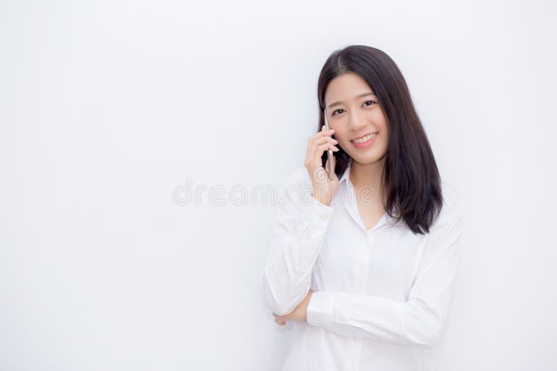 Mooie jonge Aziatische vrouw mobiele telefoon spreken en glimlach die zich op cementachtergrond bevinden royalty-vrije stock afbeeldingen