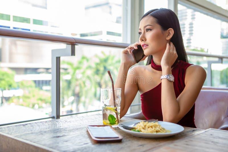 Mooie jonge Aziatische vrouw in rode kledingszitting in het restaurant die uit het venster die met smartphone roepen kijken geluk royalty-vrije stock fotografie
