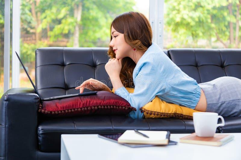 Mooie jonge Aziatische vrouw werkt op haar computer in haar woonkamer thuis royalty-vrije stock foto's