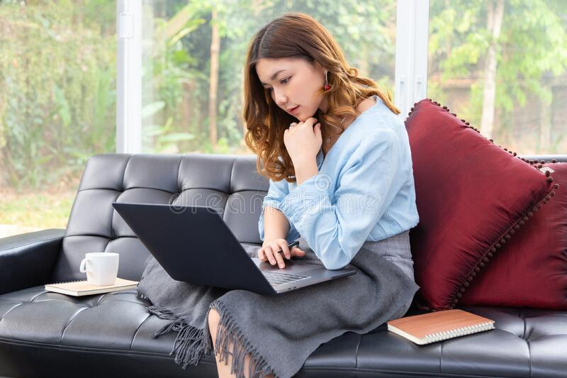 Mooie jonge Aziatische vrouw werkt op haar computer in haar woonkamer thuis stock foto's