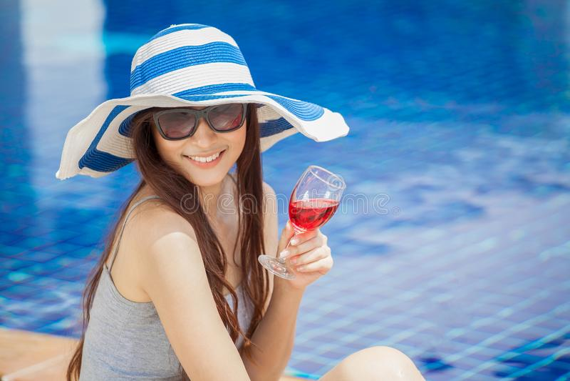 mooie Jonge Aziatische vrouwen met dranken op de zomerpartij dichtbij het zwembad Gelukkige meisjes in grote hoed en glazen het o stock afbeelding
