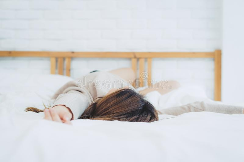 Mooie jonge Aziatische vrouwenslaap in bed in de ochtend De aantrekkelijke Aziatische bedtijd van het meisjesgebruik in haar comf stock fotografie