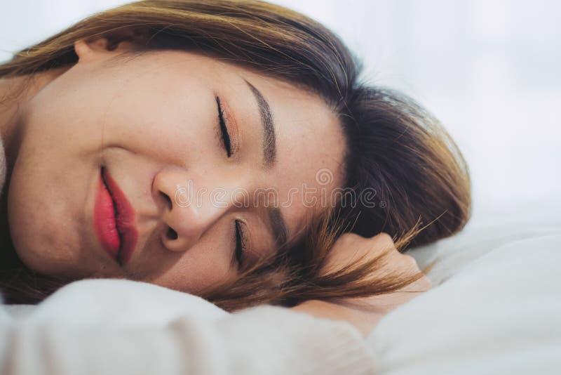 Mooie jonge Aziatische vrouwenslaap in bed in de ochtend De aantrekkelijke Aziatische bedtijd van het meisjesgebruik in haar comf royalty-vrije stock afbeelding