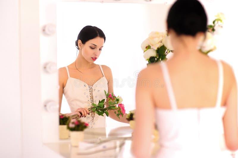 Mooie jonge ballerina die zich tegen spiegel bevinden stock afbeelding