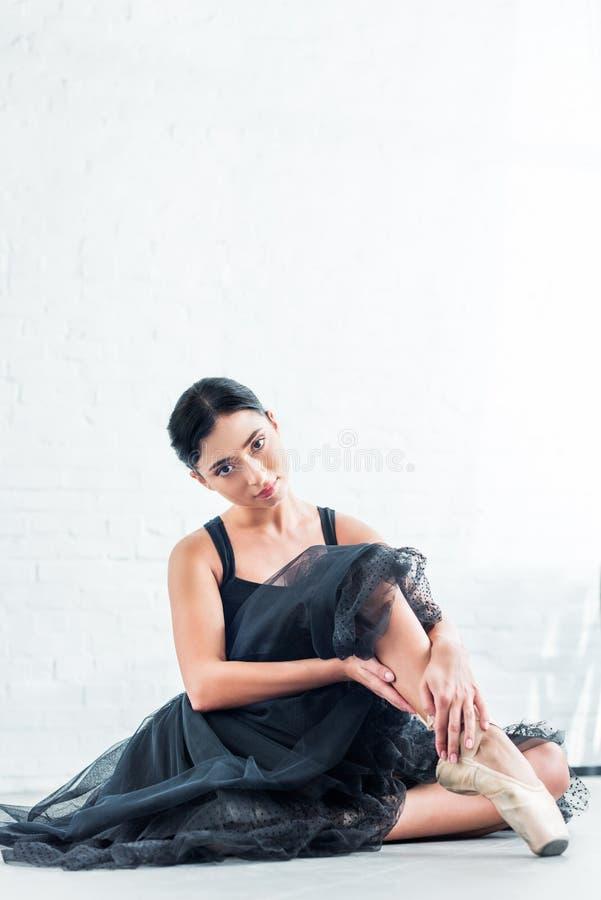 mooie jonge ballerina in zwarte tutu zitting en het bekijken camera stock fotografie