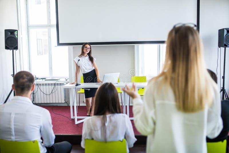 Mooie, jonge bedrijfsvrouw die een presentatie in een conferentie geven, die het plaatsen ontmoeten stock fotografie