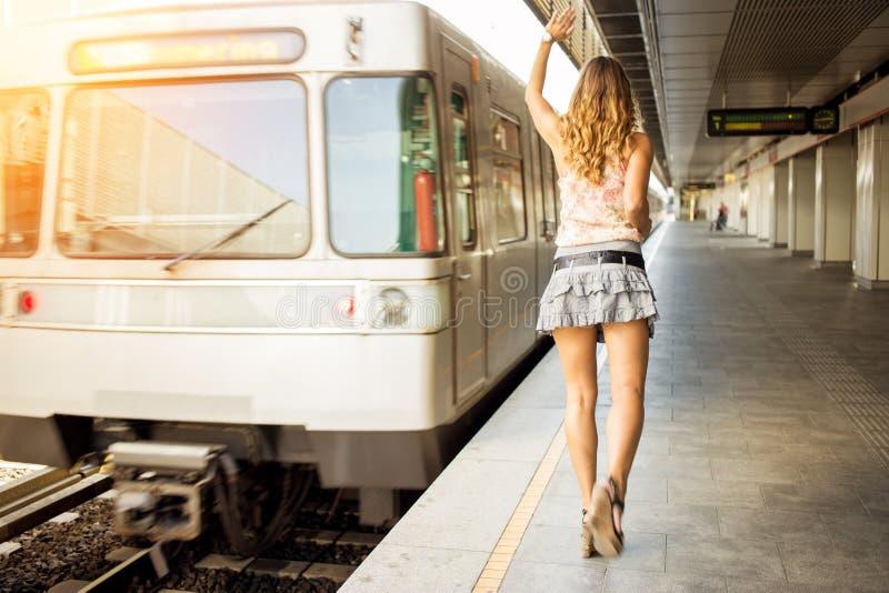 Mooie jonge bedrijfsvrouw die na trein lopen stock foto