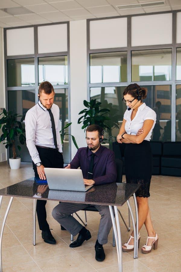 Mooie jonge bedrijfsvrouw en businessmans in hoofdtelefoons die laptops met behulp van terwijl het werken in bureau royalty-vrije stock afbeeldingen