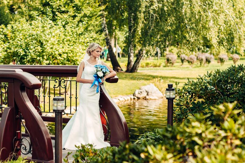 Mooie jonge blonde bruidtribunes op een brug in een exotisch park royalty-vrije stock afbeelding