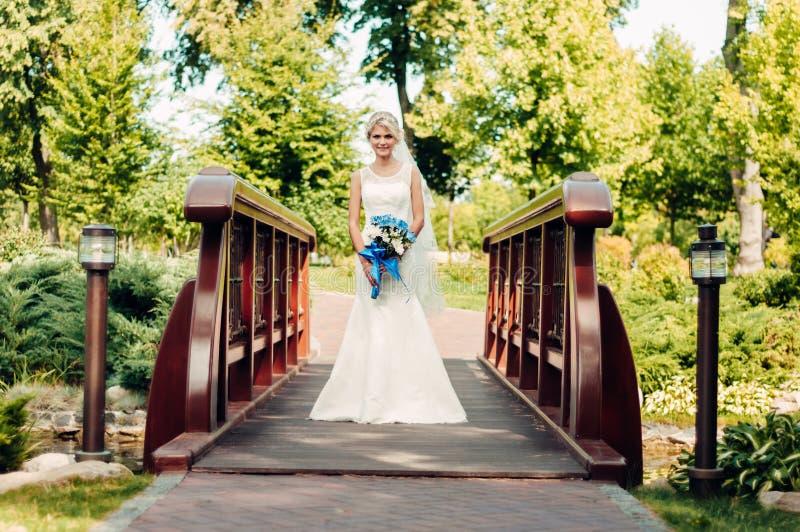 Mooie jonge blonde bruidtribunes op een brug in een exotisch park royalty-vrije stock afbeeldingen