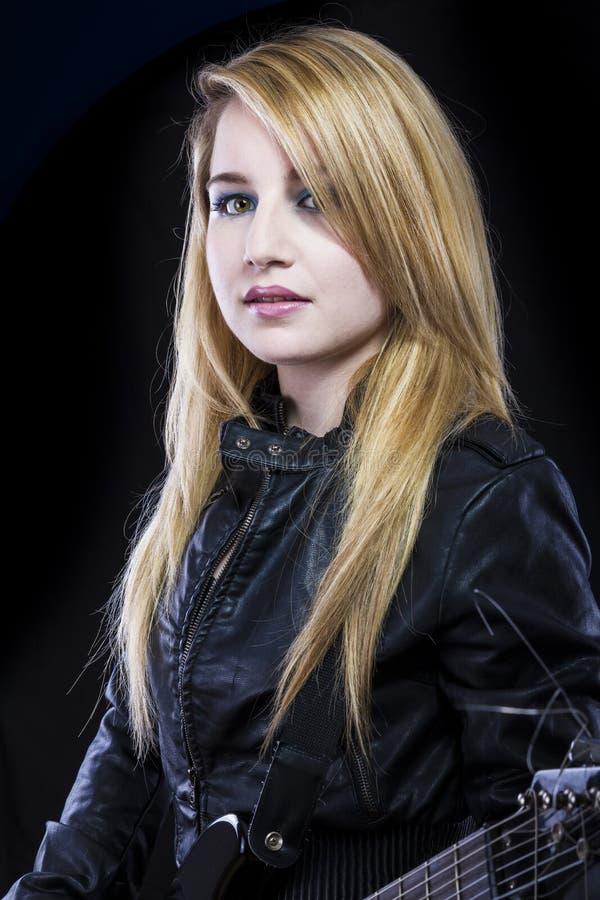 Mooie jonge blonde die met sexy ogen elektrische gitaar spelen royalty-vrije stock fotografie