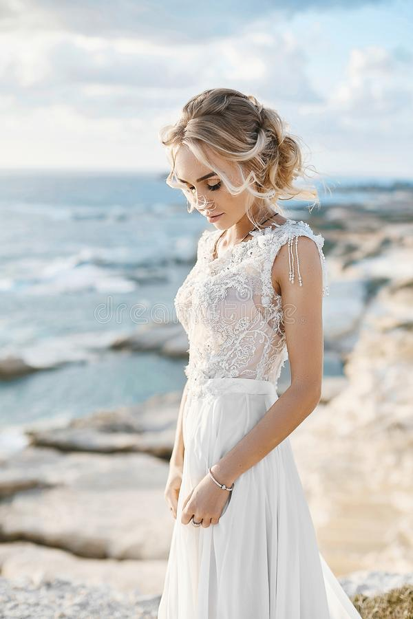 Mooie jonge blonde modelvrouw met naakte make-up in een modieuze huwelijkskleding die bij de overzeese kust in Cyprus lopen stock fotografie