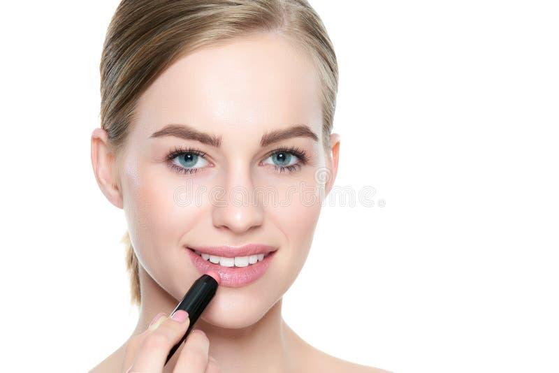 Mooie jonge blonde vrouw die met sexy volledige lippen de lippenstift van de koraalkleur toepassen Schoonheidsportret over witte  stock foto's