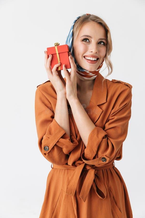 Mooie jonge blonde mooie vrouw die zijdesjaal stellen dragen geïsoleerd over de witte huidige doos muur van de achtergrondholding royalty-vrije stock fotografie