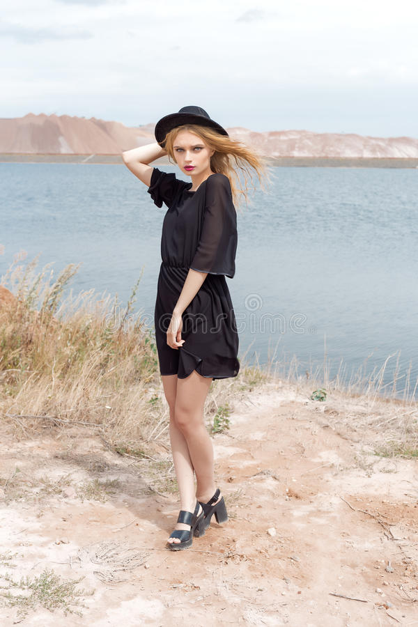 Mooie jonge blonde vrouw in een zwarte kleding en een lichte zwarte hoed in de woestijn en de wind die haar haar in een hete de z stock foto's