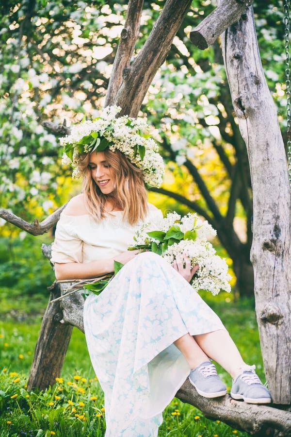 Mooie jonge blonde vrouw in lilac kroon op een schommeling royalty-vrije stock foto's