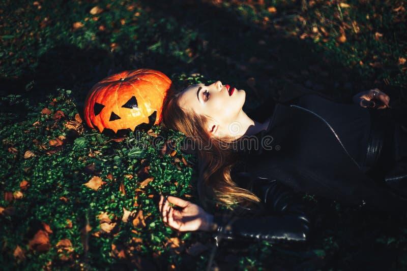 Mooie jonge blonde vrouw met extravagante samenstelling in een zwart leerjasje met wijd open ogen en een open mond met a stock foto's
